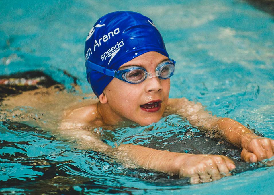 School aged child learning to swim