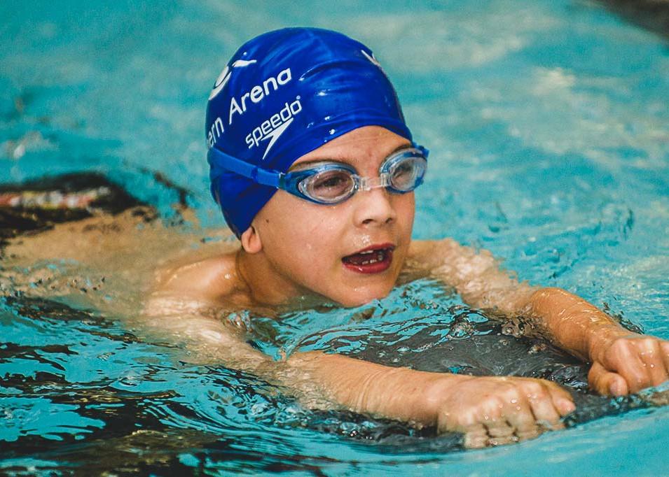 Boy kicking with kick board wearing cap and goggles