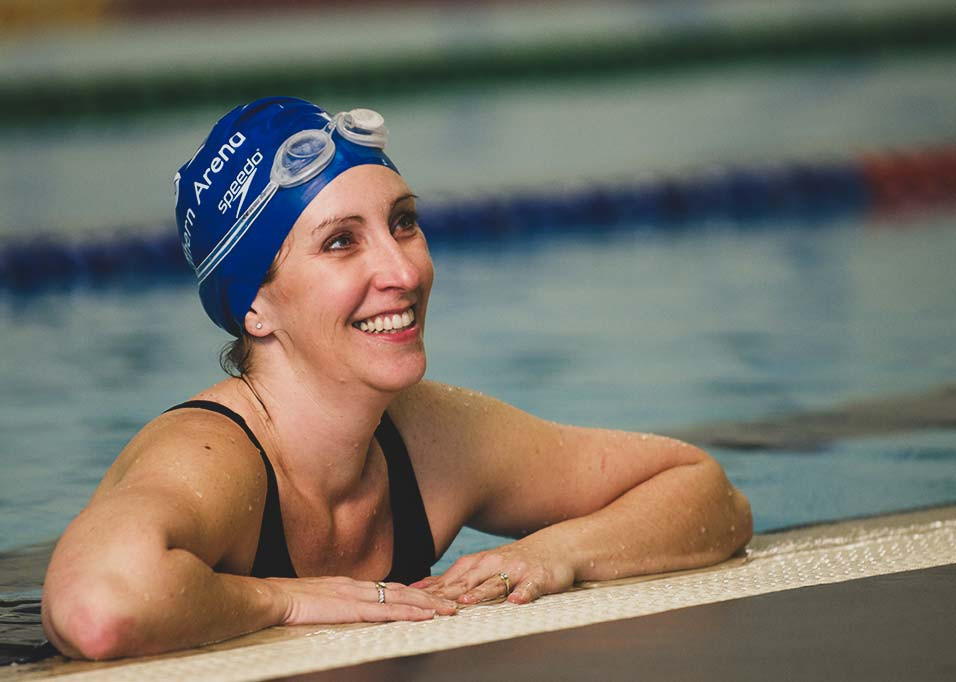 lady on side of the pool wearing cap and goggles smiling