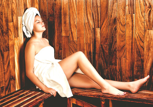 Woman lying back and relaxing with her head against the sauna wall she has a towel wrapped around her body and one wrapped in her hair her legs are on the sauna bench