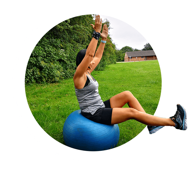 Woman performaing yoga on an exercise ball in a field
