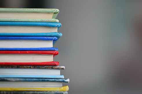 A close shot of a stack of colorful, lightly-worn books.