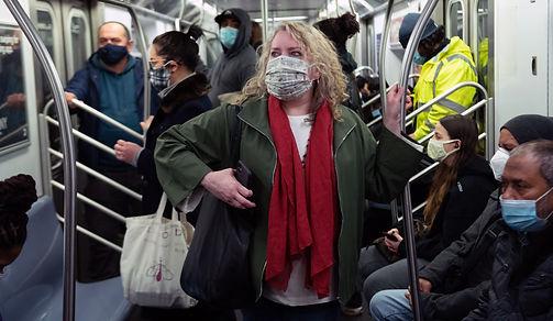 Elizabeth Caputo, masked, rides a busy subway car.
