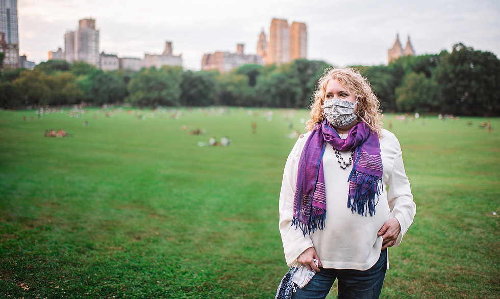 Elizabeth Caputo, wearing a white blouse, purple scarf, and face mask, stands in the Great Lawn in Central Park, with the skyline of New York City visible behind her, beyond the trees.