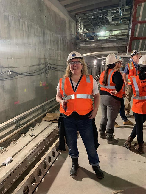 Elizabeth Caputo is wearing an orange safety vest and an MTA hardhat. She is observing the construction of a new subway tunnel.