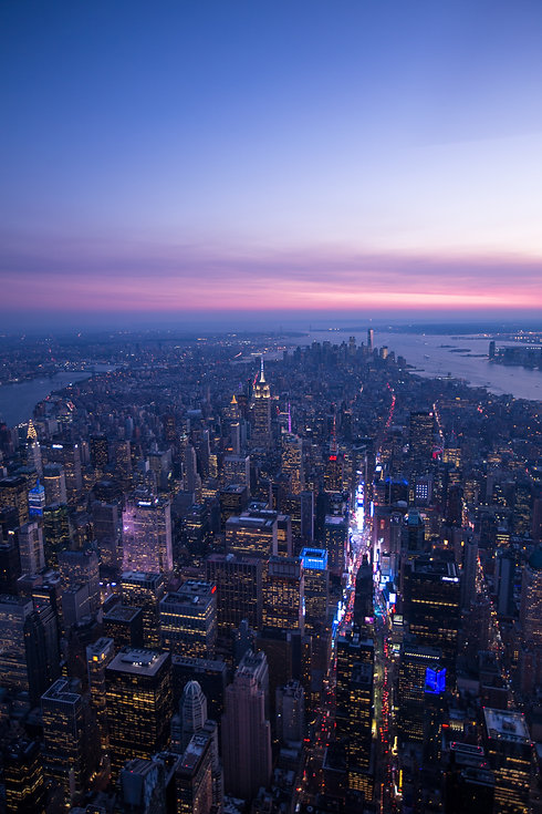 An aerial sunset shot of Manhattan, looking south from Midtown to the harbor.
