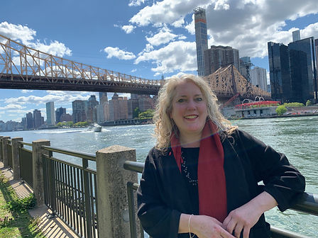 Elizabeth Caputo smiles, standing next to a river with a bridge and city skyline behind her.