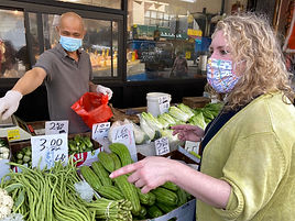 A masked Elizabeth Caputo points at a spread of produce at an outdoor market stall in Chinatown.