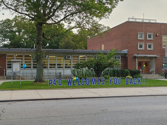 """Front of school with sign on lawn that reads """"P4Q Welcomes You Back1"""""""