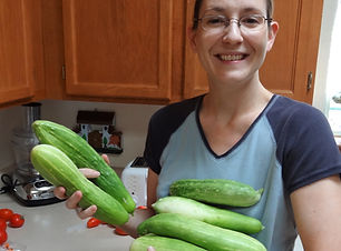 laura in the kitchen holding cucumbers.j
