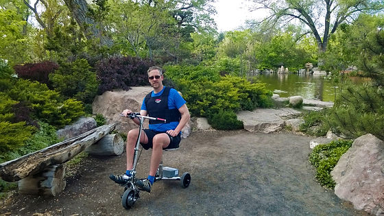 ActiveMSers Dave Bexfield on a travel scooter at a park