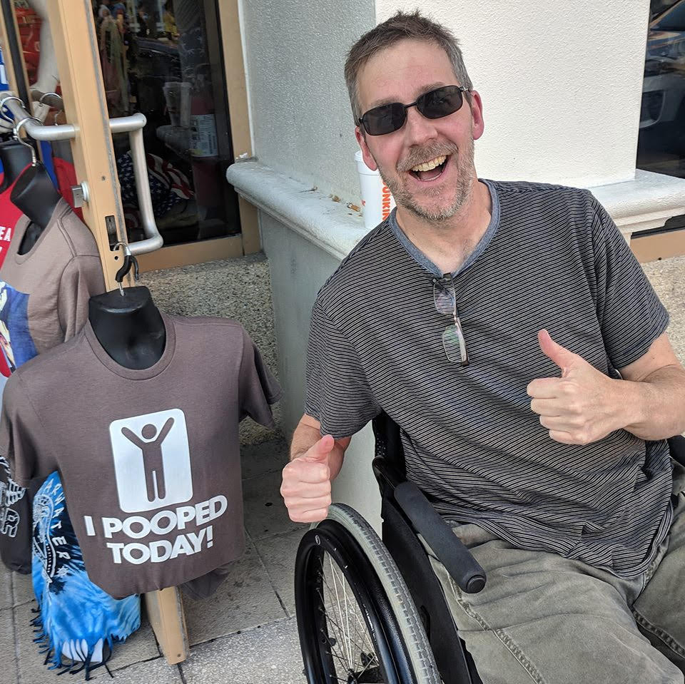Dave in a wheelchair with an I Pooped Today shirt