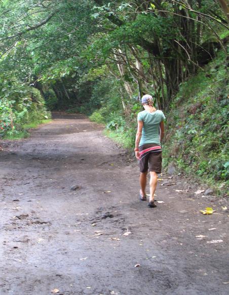 Pro triathlete Kelly Williamson walking down a dirt trail