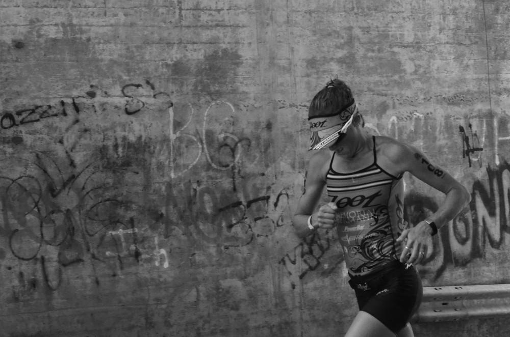 triathlete Kelly Williamson running under a bridge