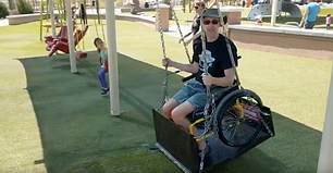 dave in a wheelchair swing at a park abo