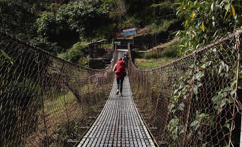 Laura with red backpack walking over a hanging bridge on the way to Ulleri, Nepal (by Hungrigaufmeer)