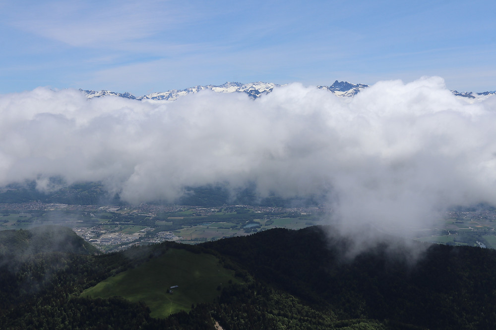View of the snowy mountains of the Alps with clouds in the front