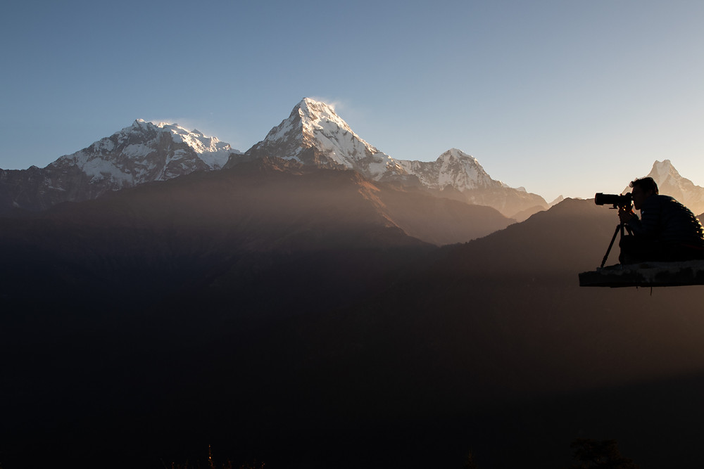 Photographer with his camera during the sunrise on the Poon Hill with the mountains in the background (by Hungrigaufmeer)