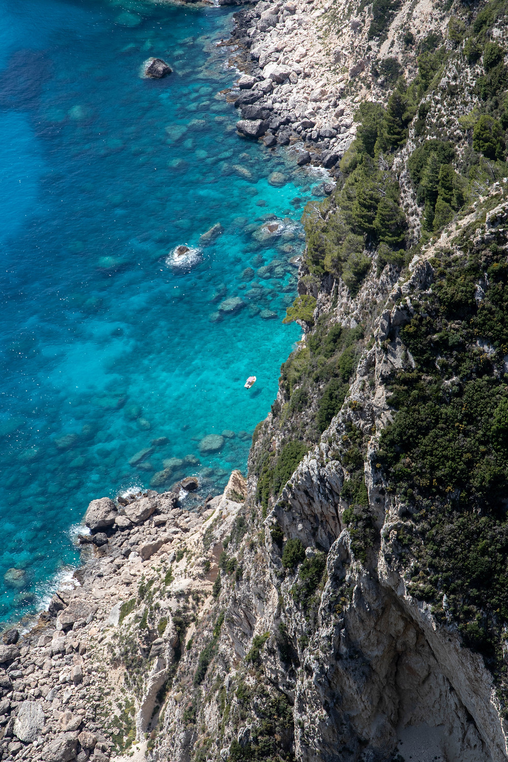 Small white boat in the blue water in front of rocky cliffs in Corfu (by Hungrig auf Meer)