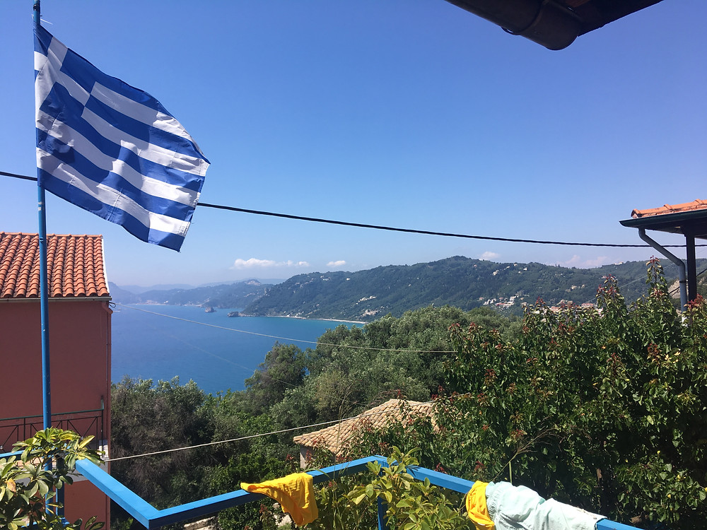 View from the terrace of Angela's Taverna with flag of Greece and ocean in the back (by Hungrig auf Meer)