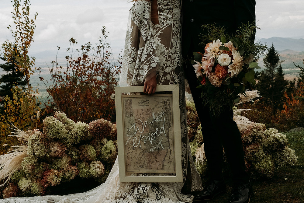 """A couple is holding a custom """"We Eloped"""" sign on top of Whiteface Mountain in New York's Adirondack High Peaks Region"""
