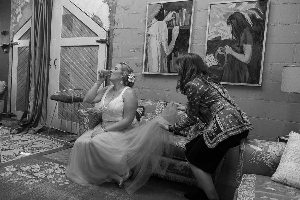 A bride drinks soda while a bridesmaid fluffs her dress