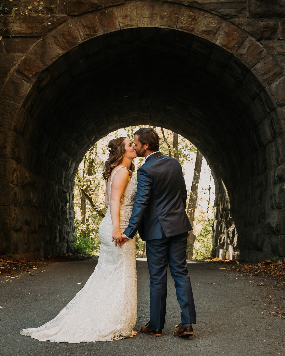 A Couple Kisses Under a Bridge After Exchanging Vows in Upstate New York