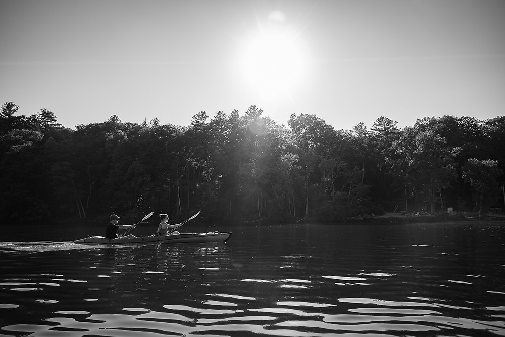 A black and white image of a couple kayaking together during their outdoor adventure engagement session with Outdoor Chronicles Photography in Great Barrington Massachusetts.