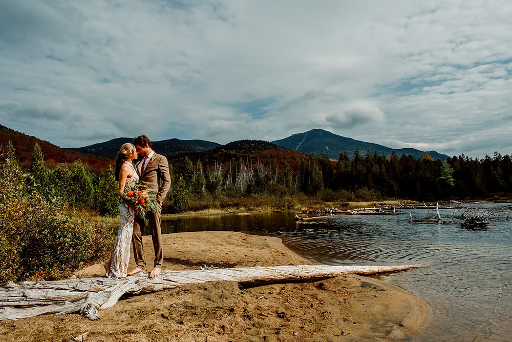 A bride in a while and gold dress is holding a bouquet of flowers. She and her groom are on an old washed up log looking at each other. They are on a secluded beach surrounded by water and mountains in Upstate NY
