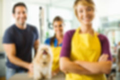 A smiling small business owner, standing in her grooming business, with an employee, a customer and his dog.