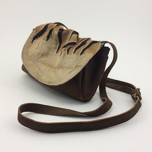 Sac bandoulière en cuir brun avec rabat en cuir poil façon zèbre.