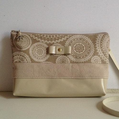 Pochette transformable en sac à main bandoulière . Cuir champagne vernis et lin