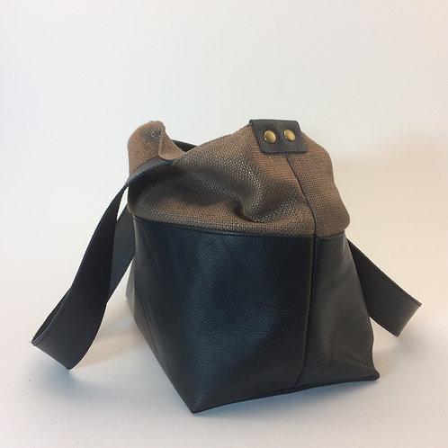 Sac à main porté épaule ou main en cuir noir et lin lamé doré cuivré. Larges anses en cuir noir.