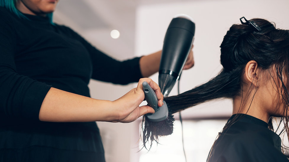 Hair stylist brushing wet hair and cutting hair in salon