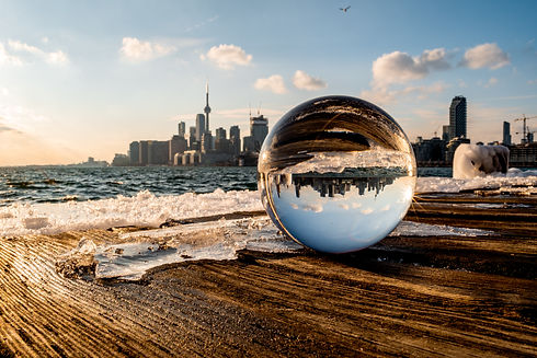 A blurry Toronto skyline behind a lensball with its reflection at Polson Pier as the sun is setting