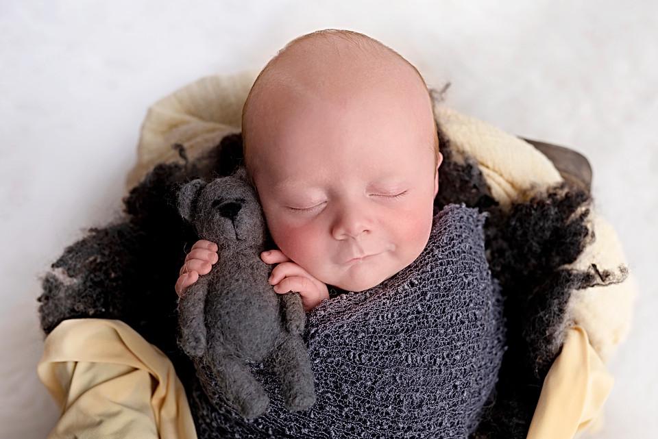 Newborn holding a teddy, Professional newborn photographer