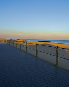 Photograph of the boardwalk, beach, and blue sky at Spring Lake NJ in the late afternoon. Photo by Jodi DiLiberto
