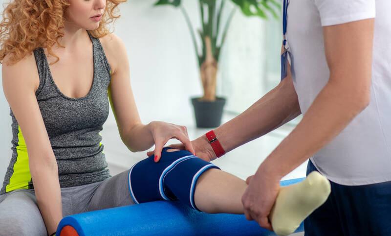 physcial therapist examining knee injury