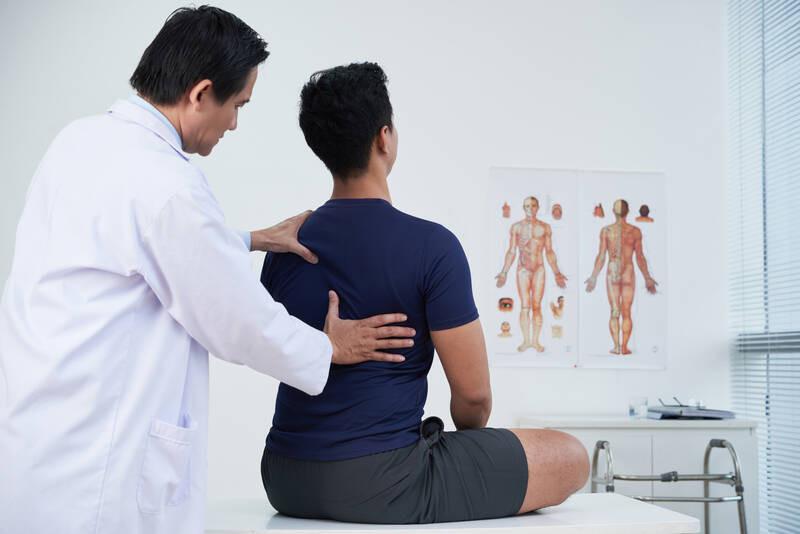 chiropractor examining back of patient