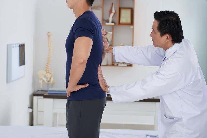 chiropractor examining patient's back