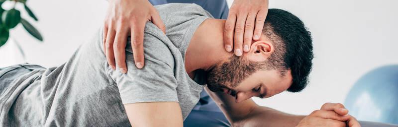 chiropractor massaging neck of patient