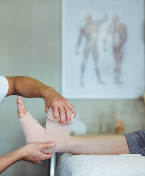 physiotherapist putting a bandage on injured foot