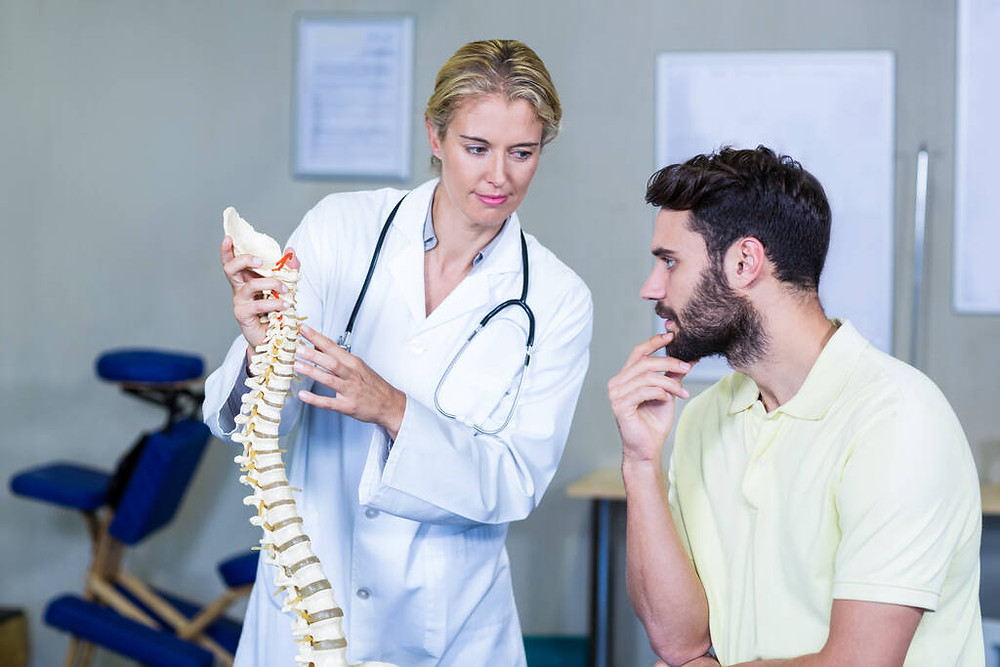 physiotherapist-explaining-spine-model-to-patient