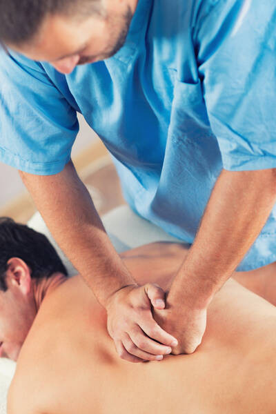 physiotherapist working on patient's back