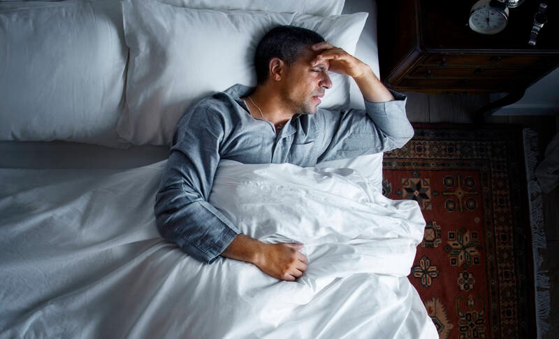 man in bed with a headache