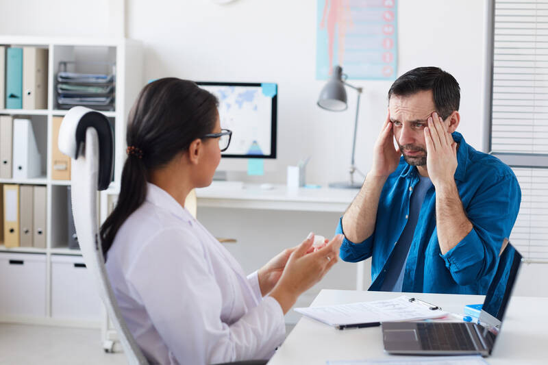 man complaining about headache to a doctor
