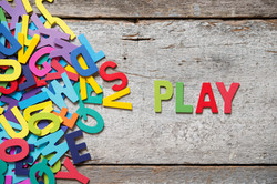 The colorful words _PLAY_ made with wooden letters next to a pile of other letters over old wooden b