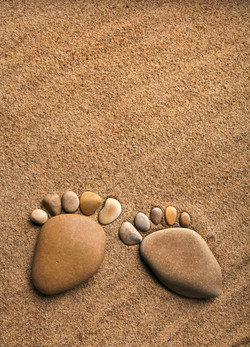 pair trace feet made of a pebble stone on the sea sand desert texture surface backdrop with copy spa