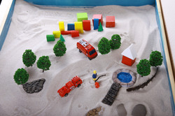 Miniature family constellations, toy fire.jpgSand therapy.jpgThe child is built in a sandbox world,