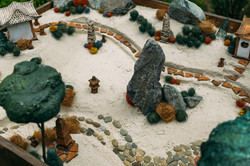 Miniature houses, toy landscape objects on the sand. Sand therapy